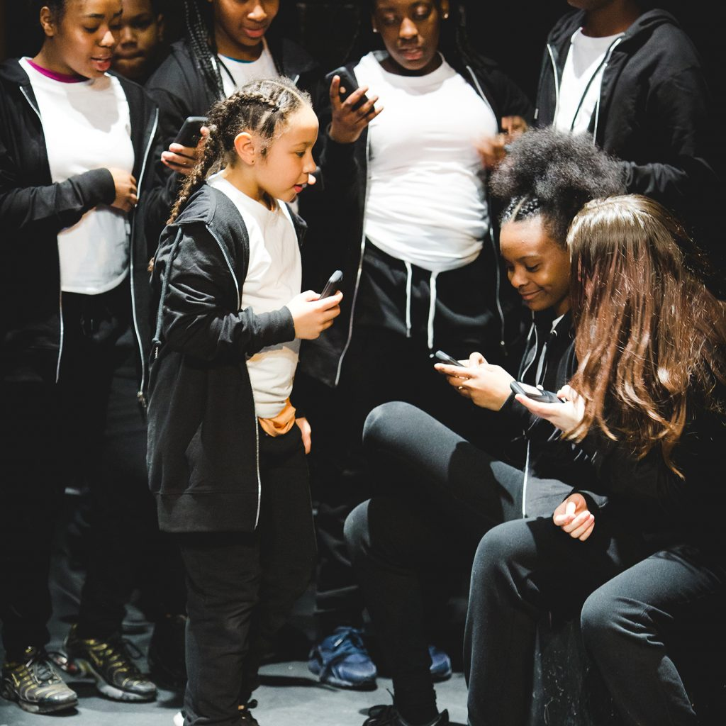 A group of young people looking at something on a mobile phone, all wearing black and white.
