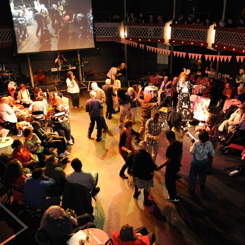 A theatre filled with people of all ages dancing, sitting at tables, with a big screen at the back.
