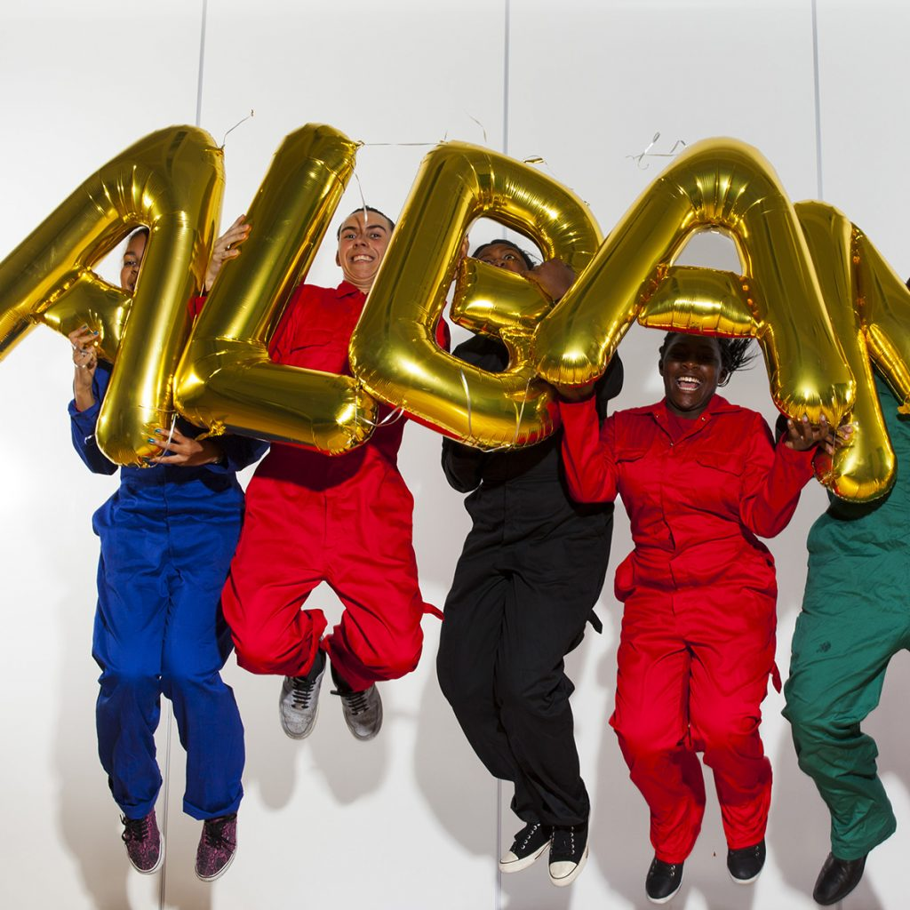 Seven young people in bright boiler suits leap in the air holding up gold balloons spelling out 'Albany' against a white background.
