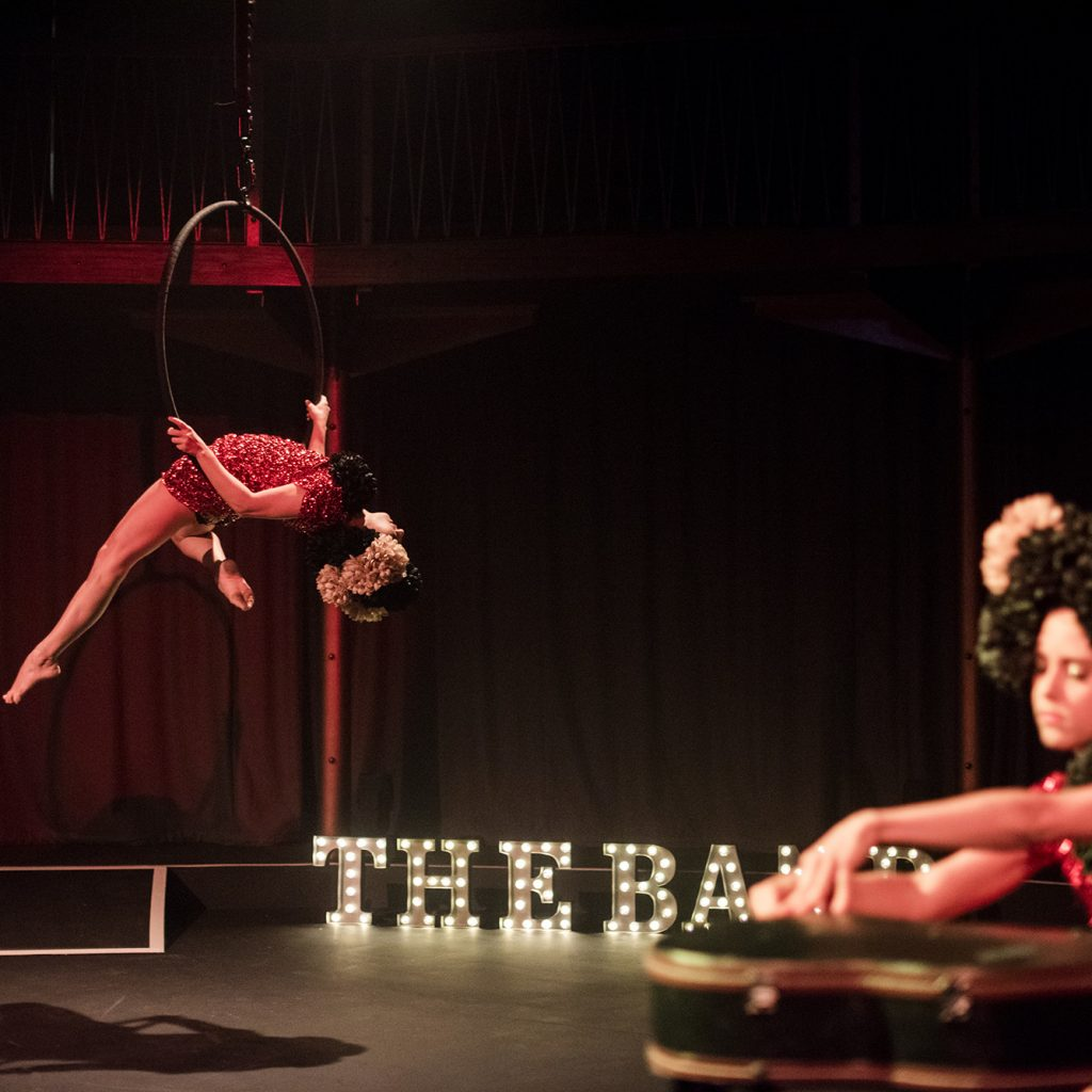 Woman in foreground, seated behind guitar case, woman in background hanging off aerial circus hoop. Both in red sequin dresses with extravagant black wigs.
