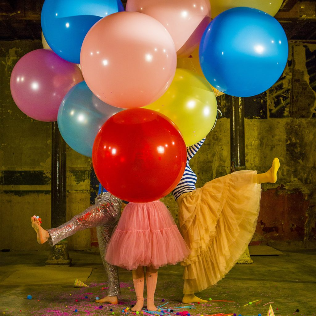 Large, bright balloons, and actors in bright costumes, their upper bodies obscured by balloons.