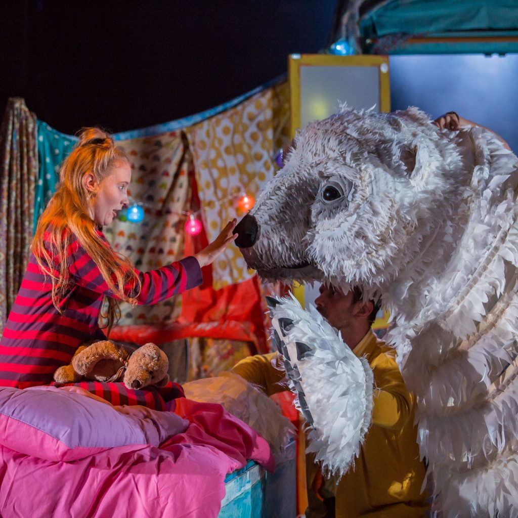 An actor in stripey pajamas, playing a young girl reaches towards the nose of a huge polar bear puppet. She is sitting on her bed which is pink.