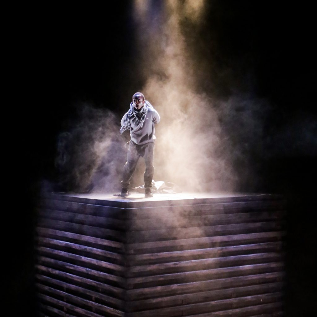 A male actor stands wreathed in smoke on top of a huge wooden box. He is lit from above.