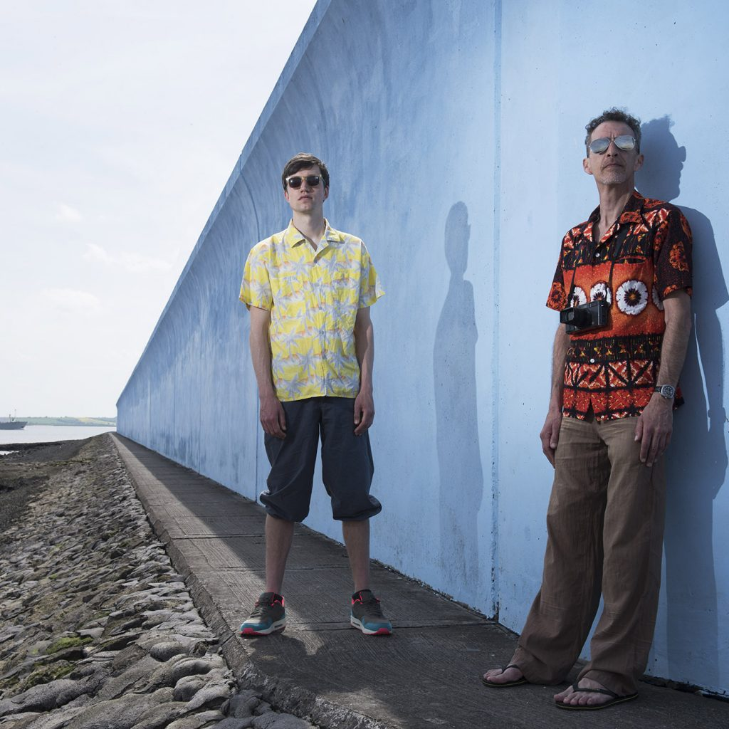 Two men in Hawaiian shirts lloking into the distance, towards the camera, leaning on a blue sea wall, stretching out behind them, all the way to the sea and the horizon