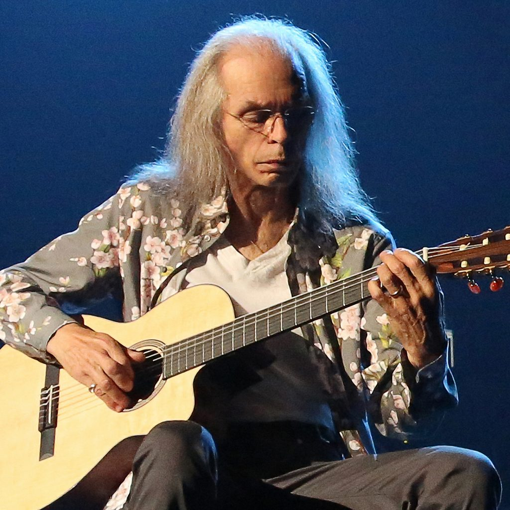 An older man with a guitar and log hair plays on a stage. He's wearing a grey shirt with pink flowers on it and black jeans.