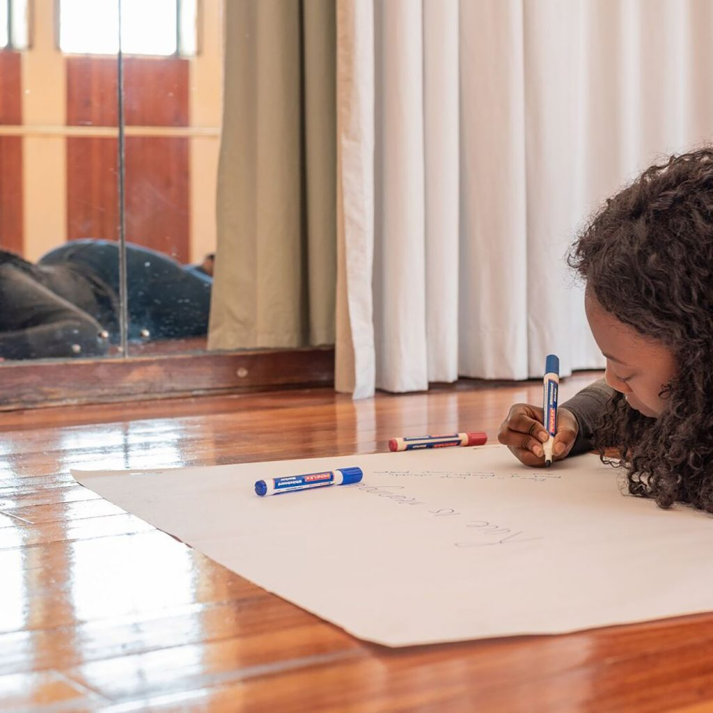 A young black woman lies on the floor of a dance studio, writing on a big piece of paper. You can see her reflection in a mirror. She is wearing a great top and jeans.