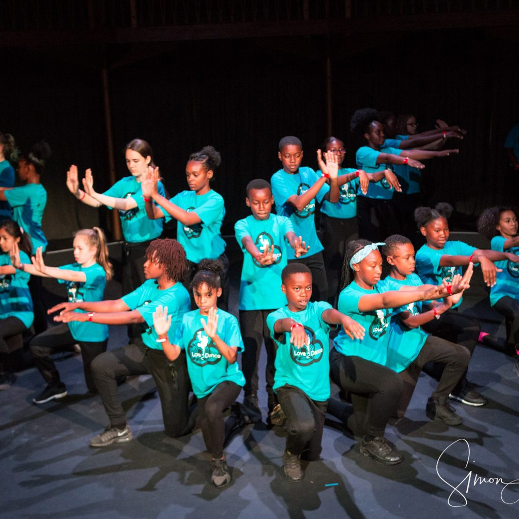 A group of young people in bright blue T-shirts and black tracksuit bottoms dance on stage.