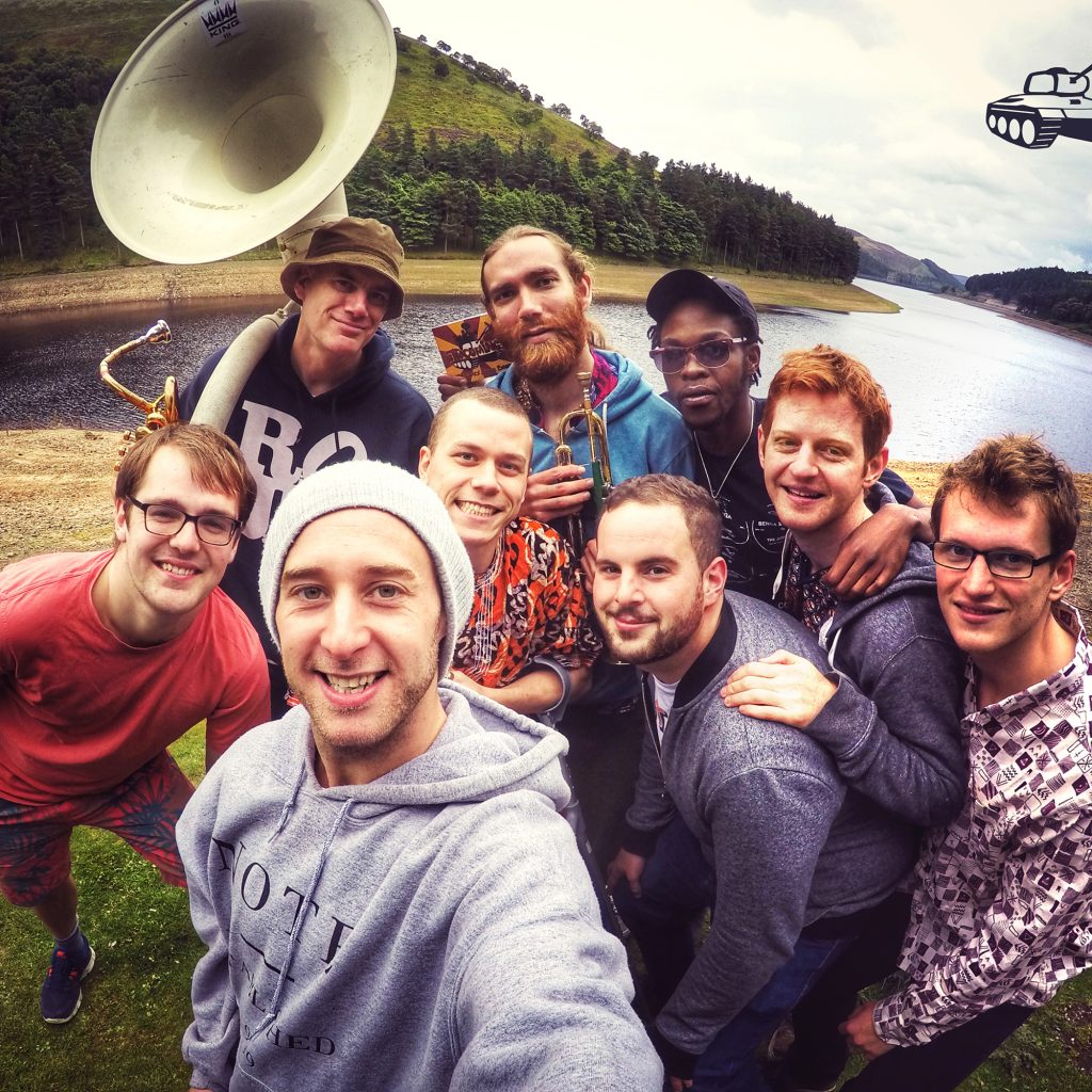 A group of 9 young men pose in front of a lake. The one on the back left has a huge brass musical instrument,