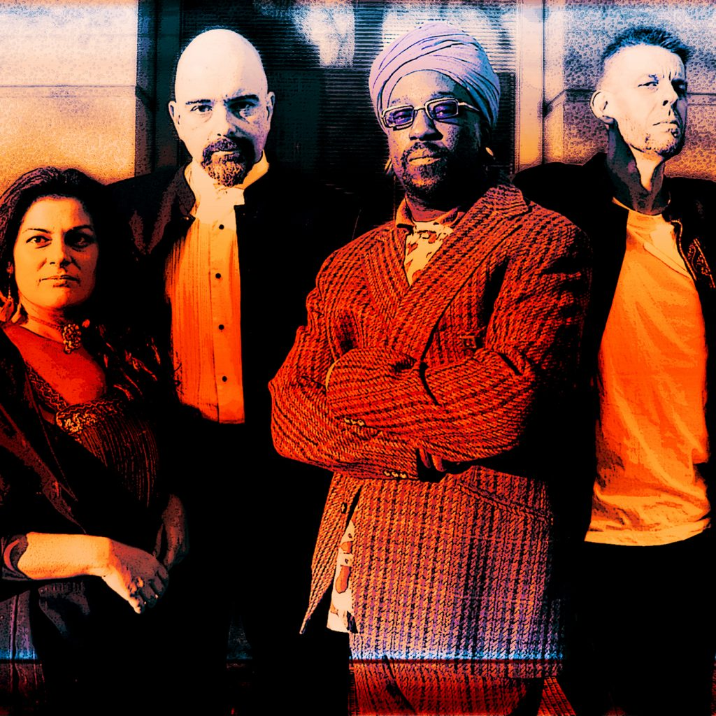 A woman and three men stand side by side. They are leaning on a railing in front of a front door and a wall. The image has an orange / sepia like colour tone.