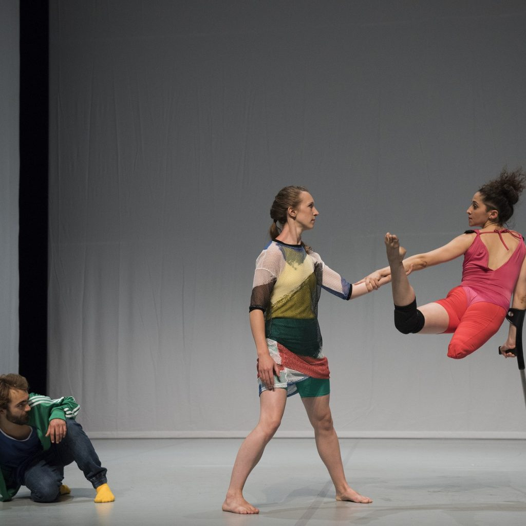 3 dancers in front of a grey background. One looks on, two dance together. One has a crutch and is balancing on it. She is missing part of her right leg.