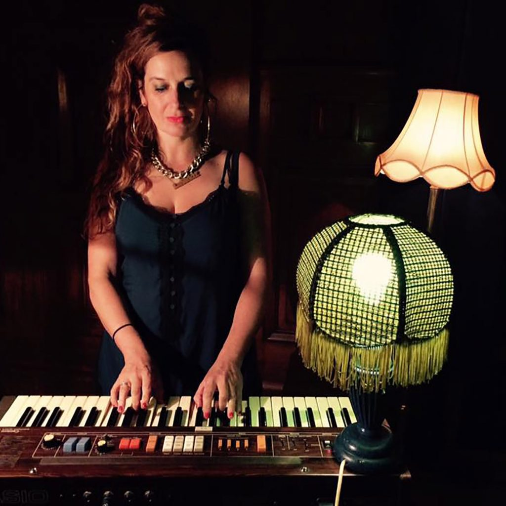 Image of a white woman with auburn hair and chunky jewelry in a blue dress. she is standing playing a keyboard with a lamp on her right and anther lamp behind her.