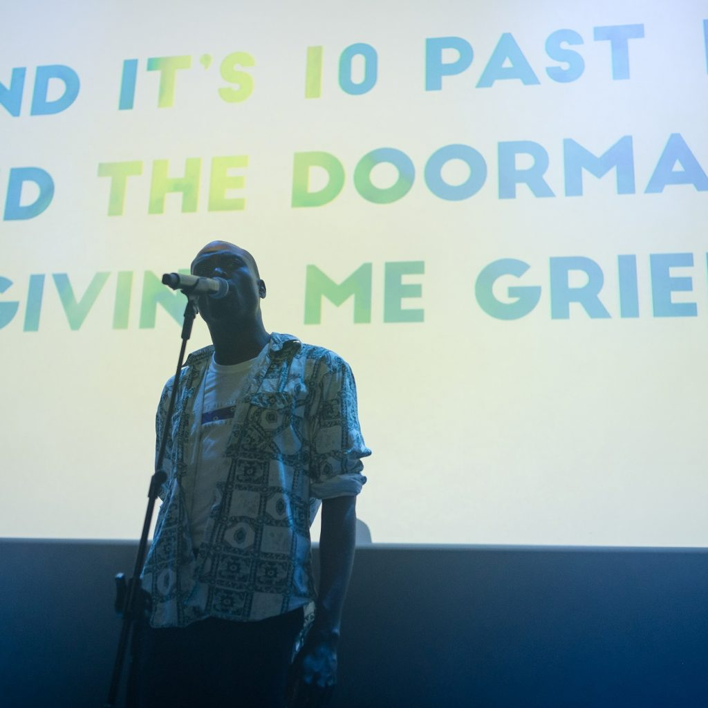 A young, black man stands on stage in front of a microphone with a screen behind with writing on it.