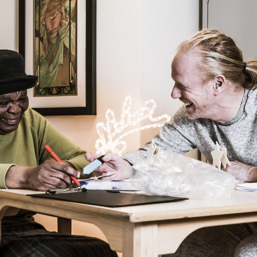 An older black woman and a younger white man seated at a table, doing craft and laughing.