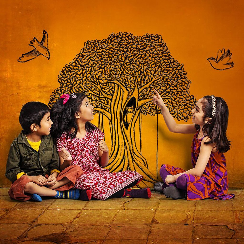Three children sit on a stone tiled floor pointing at a drawing in black ink of a tree with an owl in it and two birds which has been drawn on the wall.