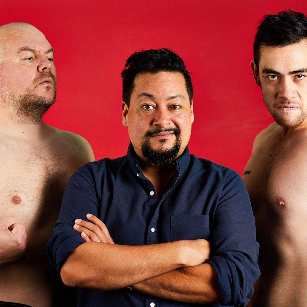 Three men - 2 topless, flashing their guns, one in a dark shirt, against a red background.