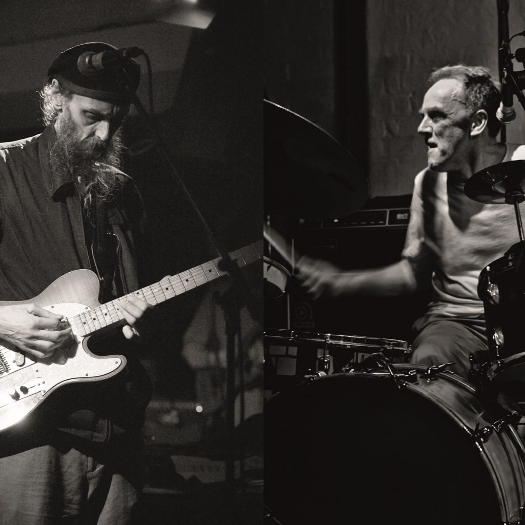 Two older white men perform on stage - one on guitar, one on drums.