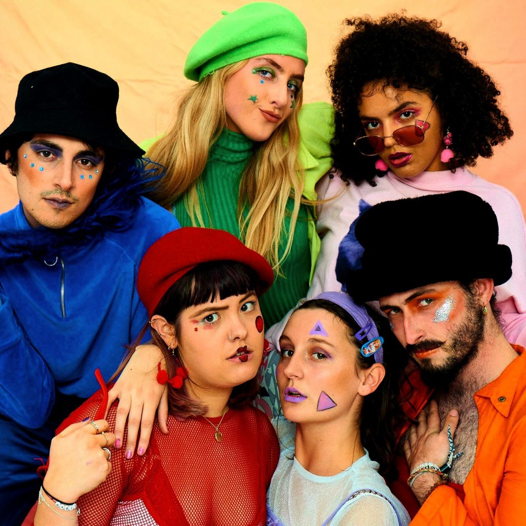 A group of young people are posing together while wearing colourful clothes and makeup.