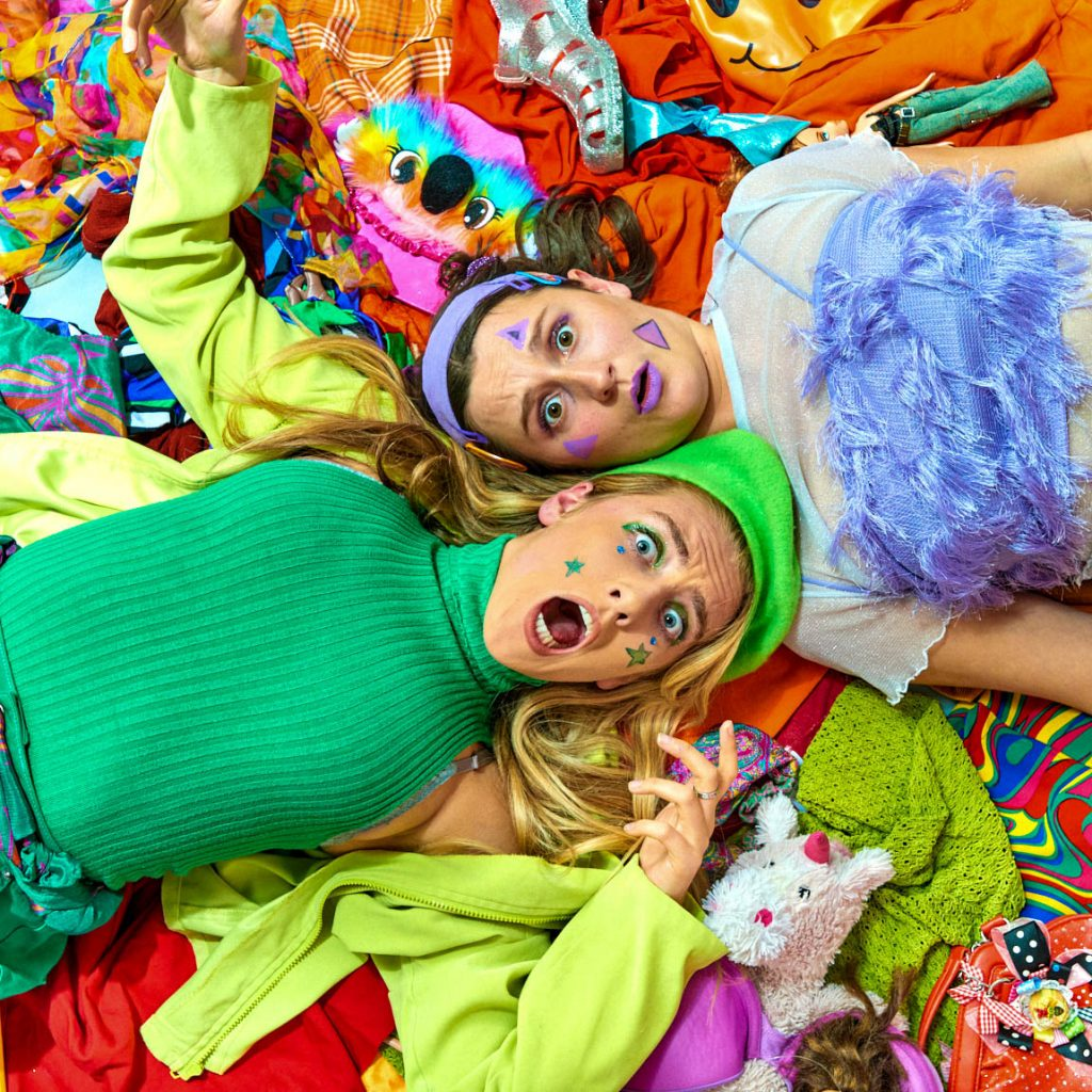 Two young women are lying on top of colourful clothes are looking up towards the camera appearing shocked and suprised.