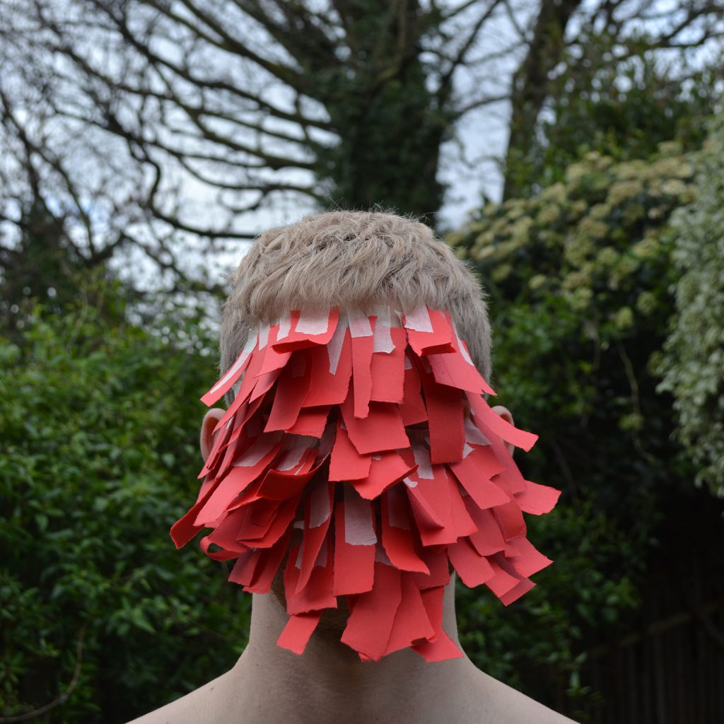 A man with strips of paper obscuring his face looks to camera.