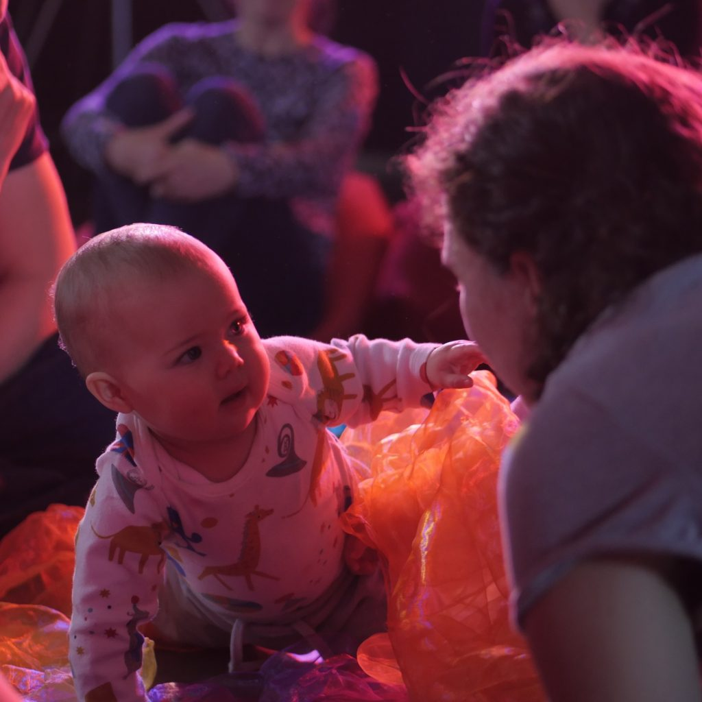 A baby reaches towards a performer, looking quizzical.