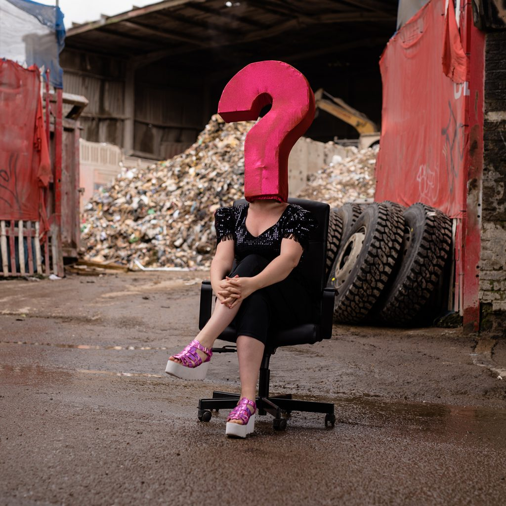 A woman sat on a seat with her legs crossed with a large pink question mark on her head covering her face.