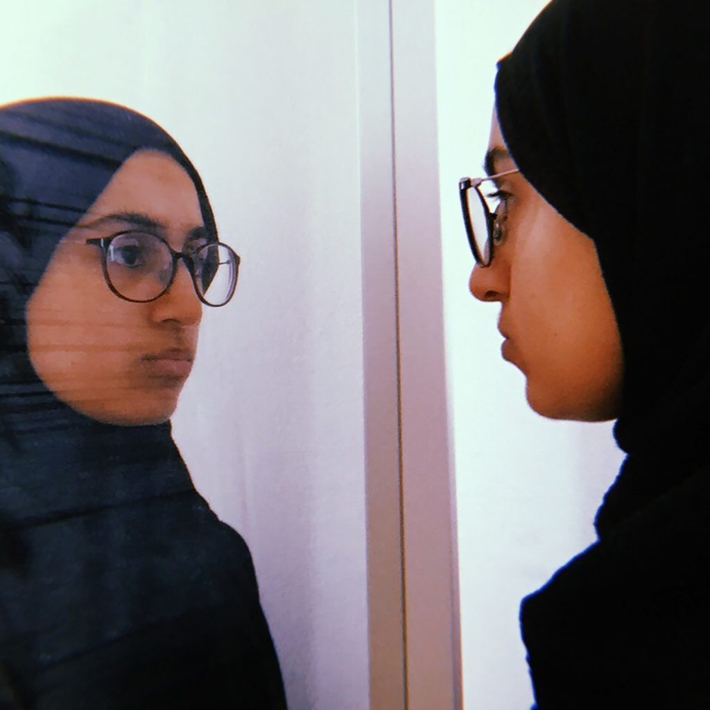A young woman in a headscarf looks at herself in the mirror.