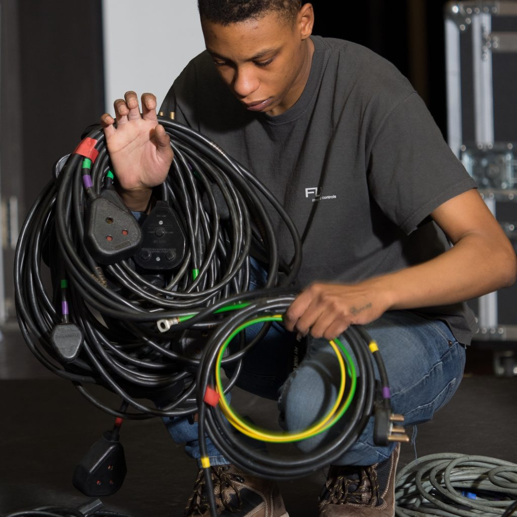 A boy is crouched down holding cables