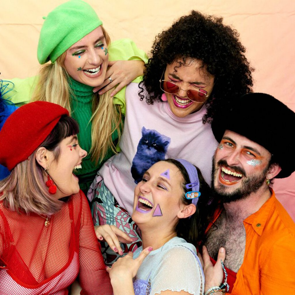 Group of performers smiling and laughing in bright coloured clothes.
