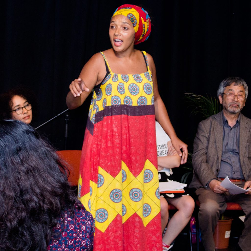 A black woman in African style clothing stands reading aloud to a room of people.