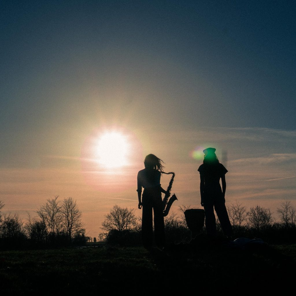 2 musicians in silhouette, outdoors against a sunset backdrop.