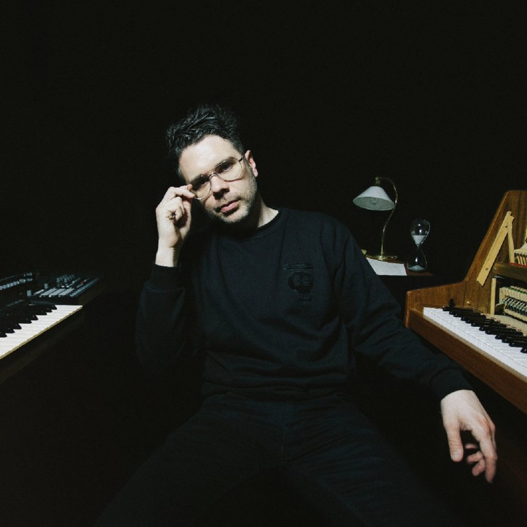 Image of a man sitting next to a piano