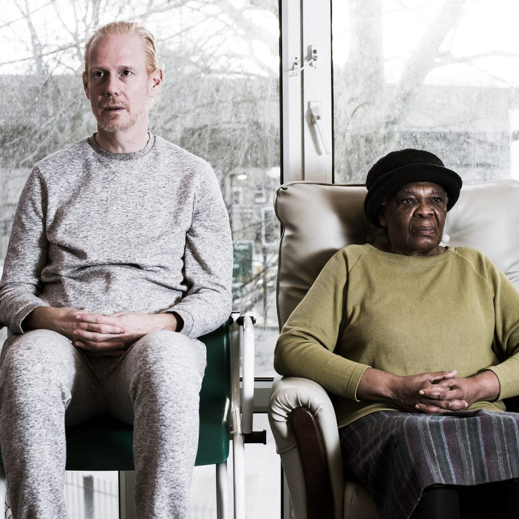 Image of two people sitting on chairs, staring straight ahead in a care home.