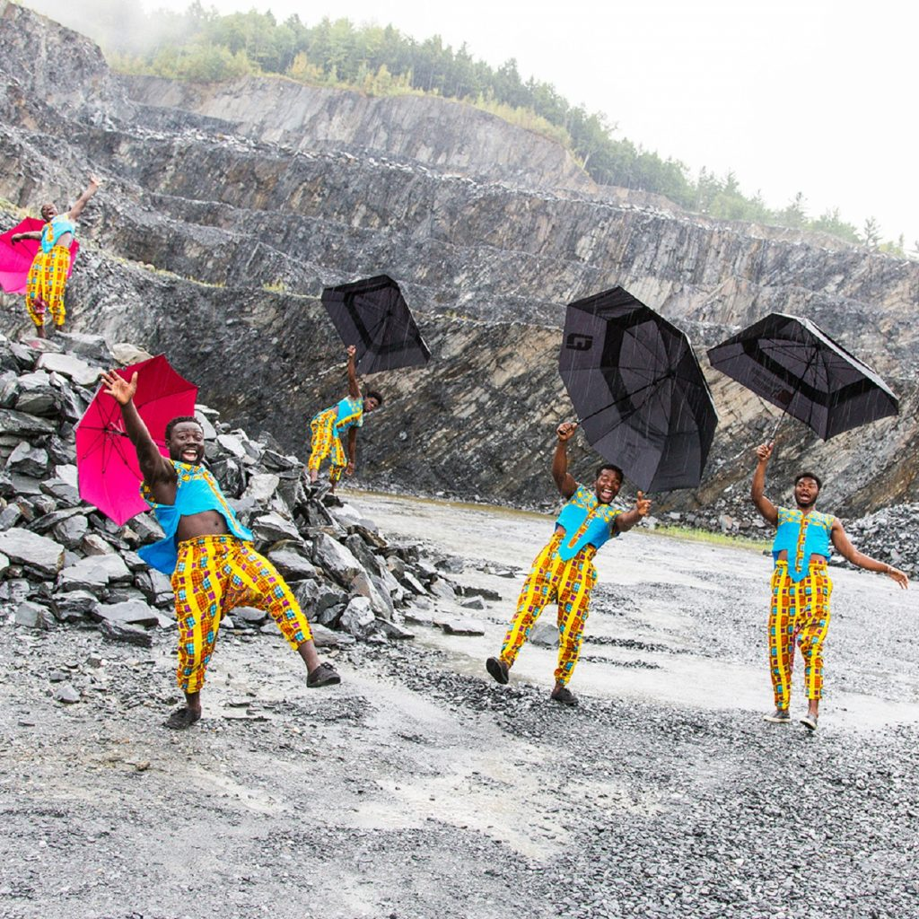Six people wearing brightly coloured clothes, holding umbrellas, dancing in the rain.
