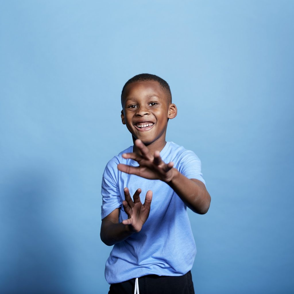 Image of a young boy standing in front of a blue backdrop, clapping.