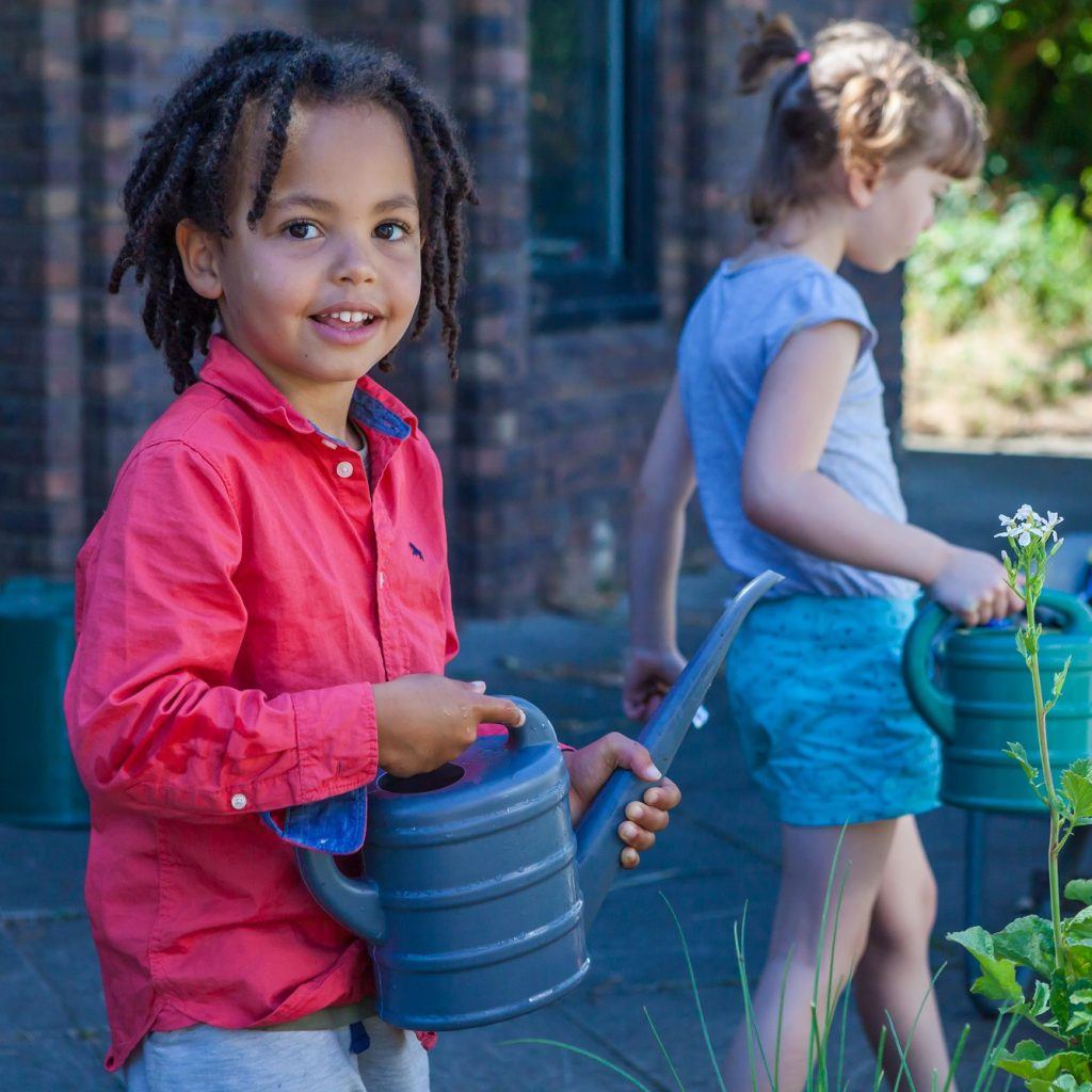 Image of a young child standing in a garden holding a watering can.