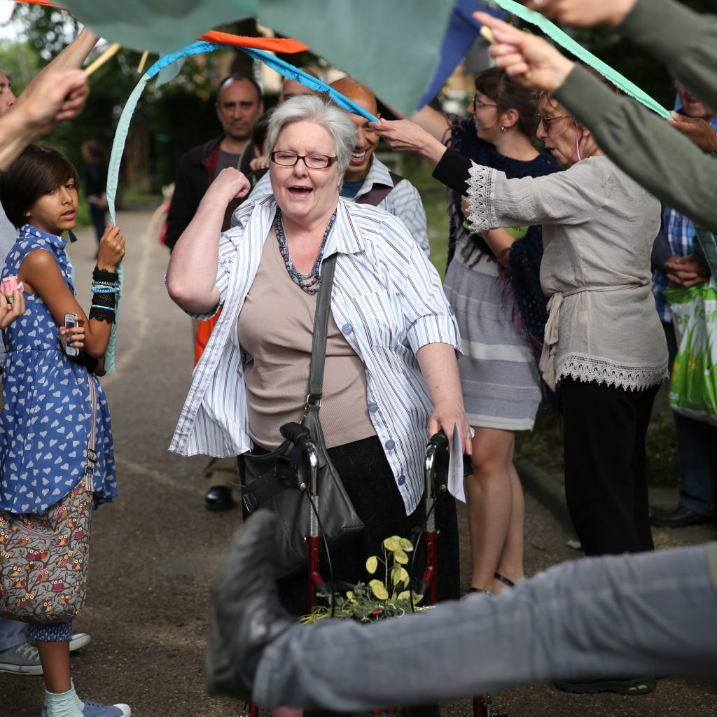 Image of an older woman walking through a crowd in a garden using a walker