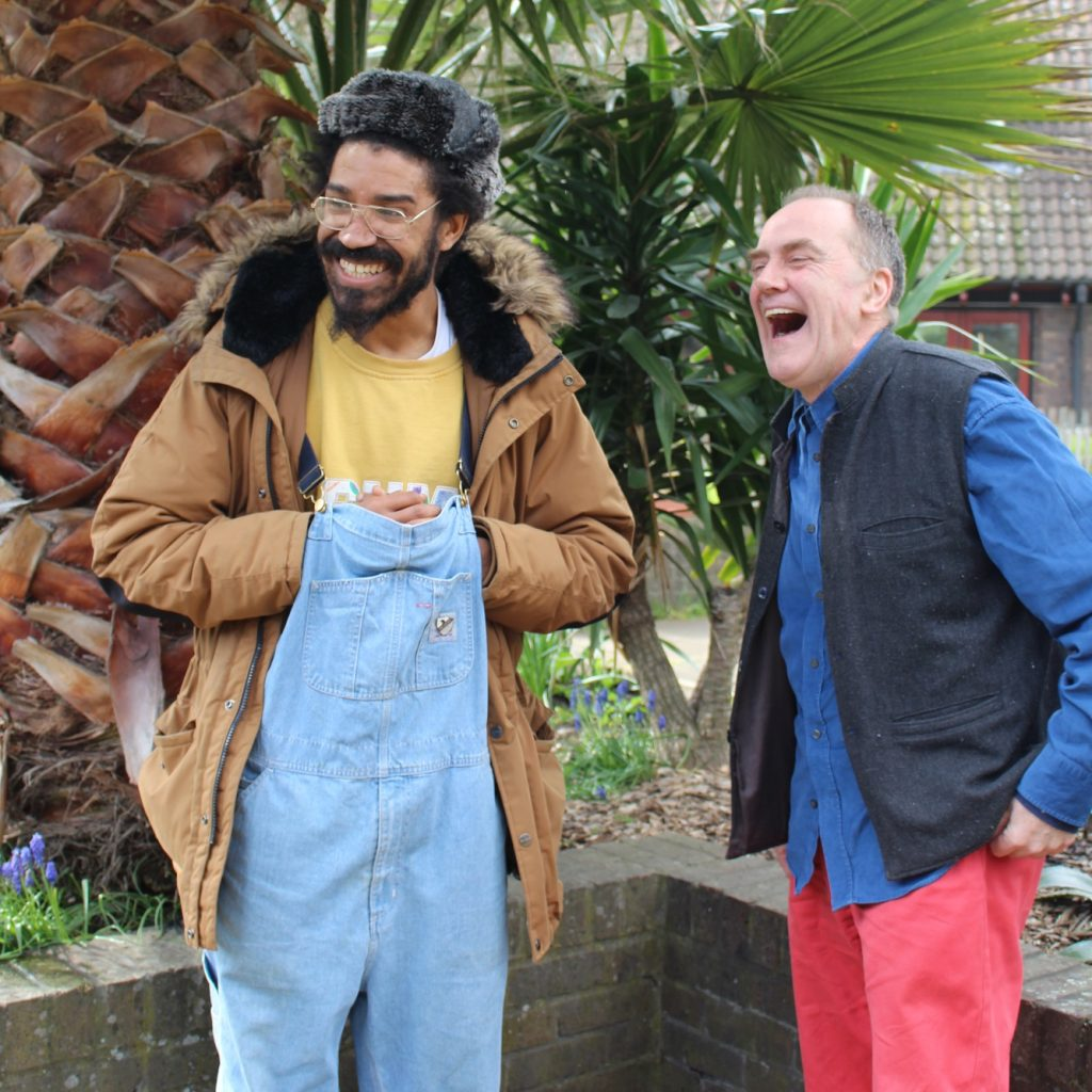 Image of two men standing in a garden, both laughing.,