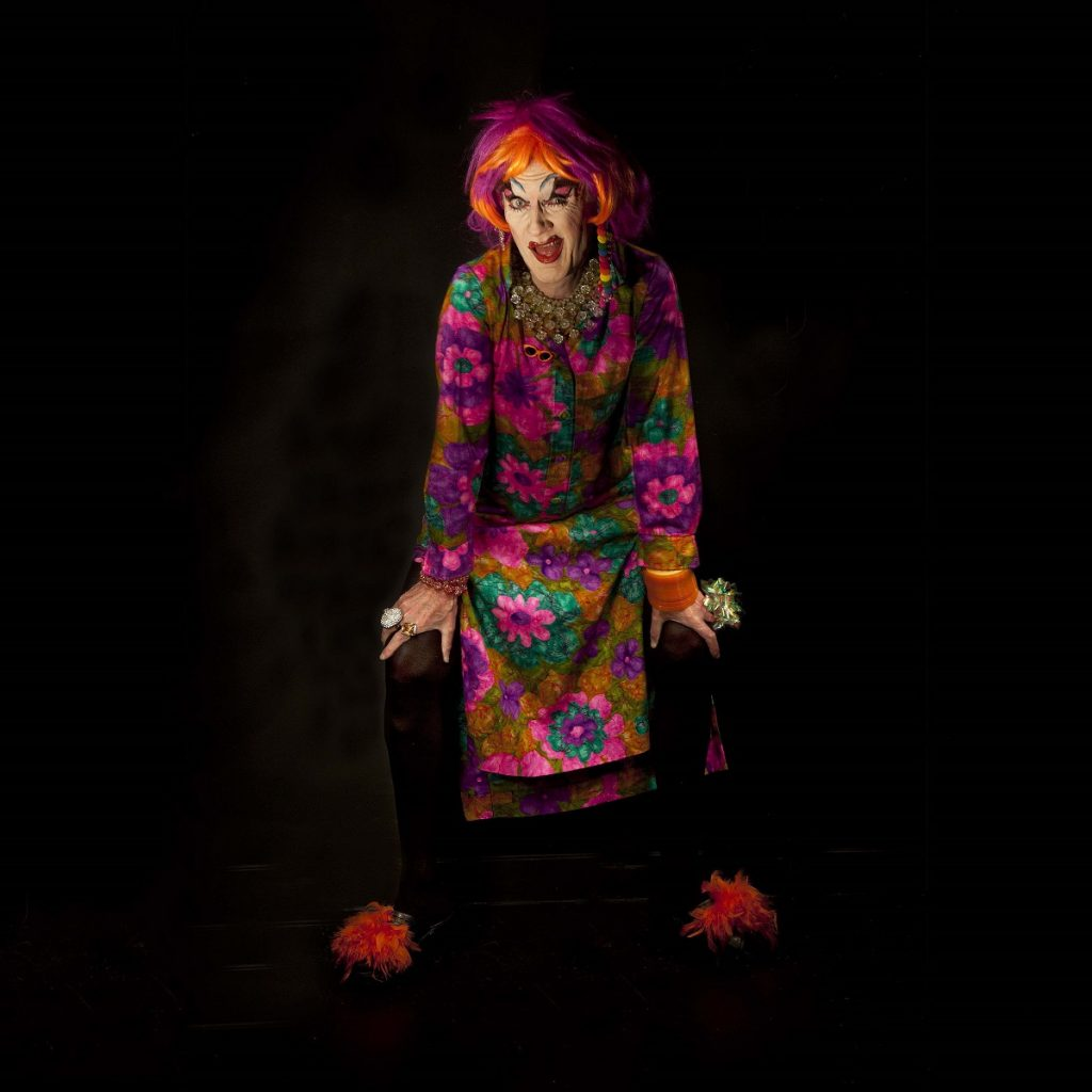 Image of a performer in brightly coloured clothes and a red wig, standing with her hands on her knees against a black background.