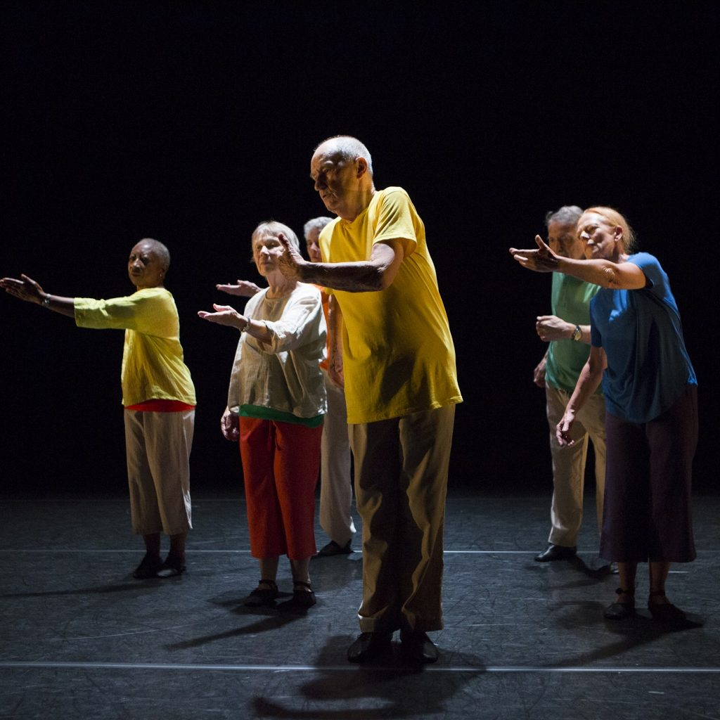 A group of people dancing on a dark stage, with one arm outstretched.