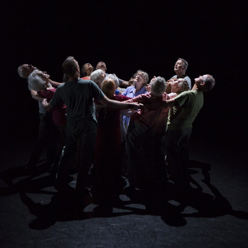 A group of people dancing on a dark stage, their arms are linked and they are leaning backwards in a circle.
