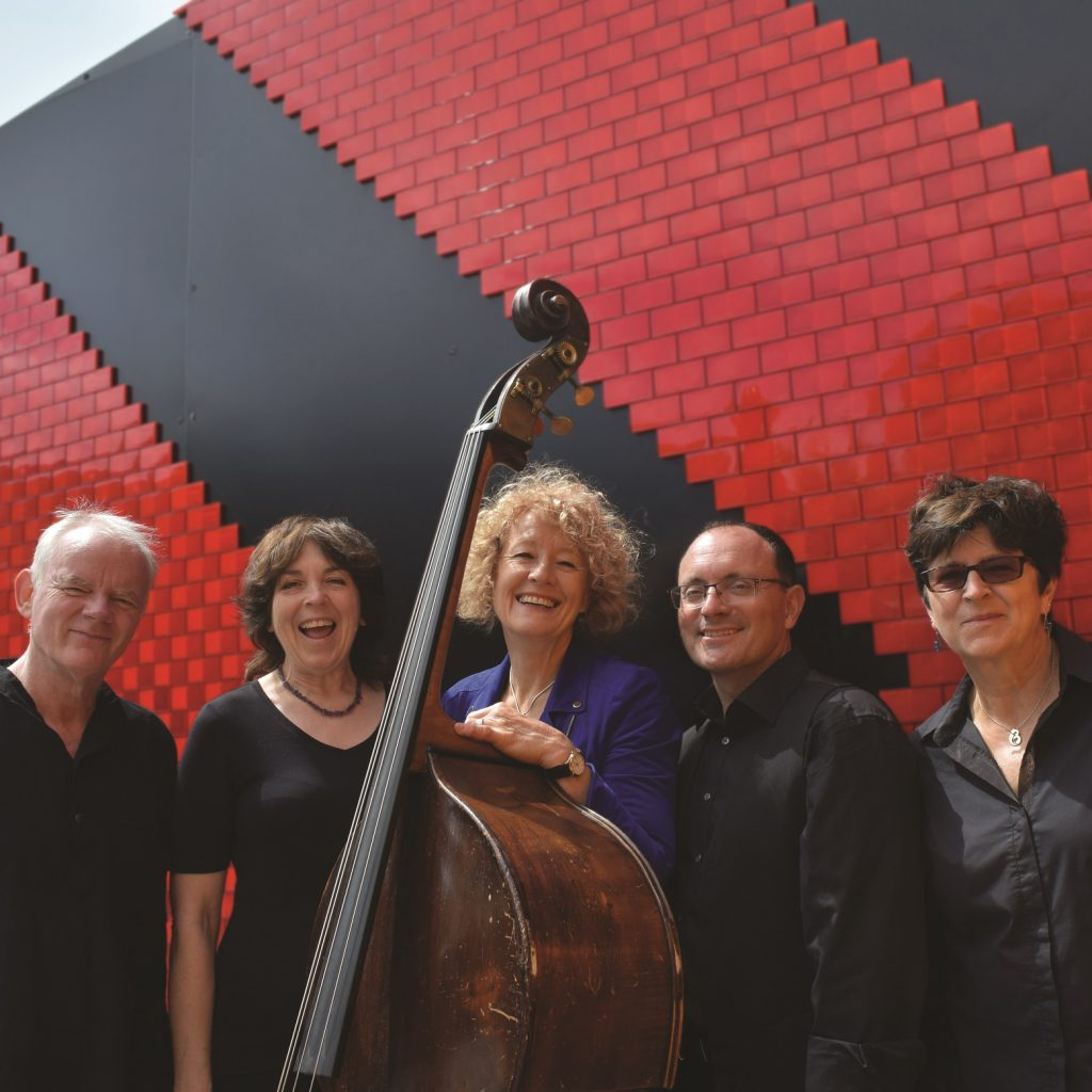 Five people dressed in black, standing behind a cello in front of a red and black striped backdrop.