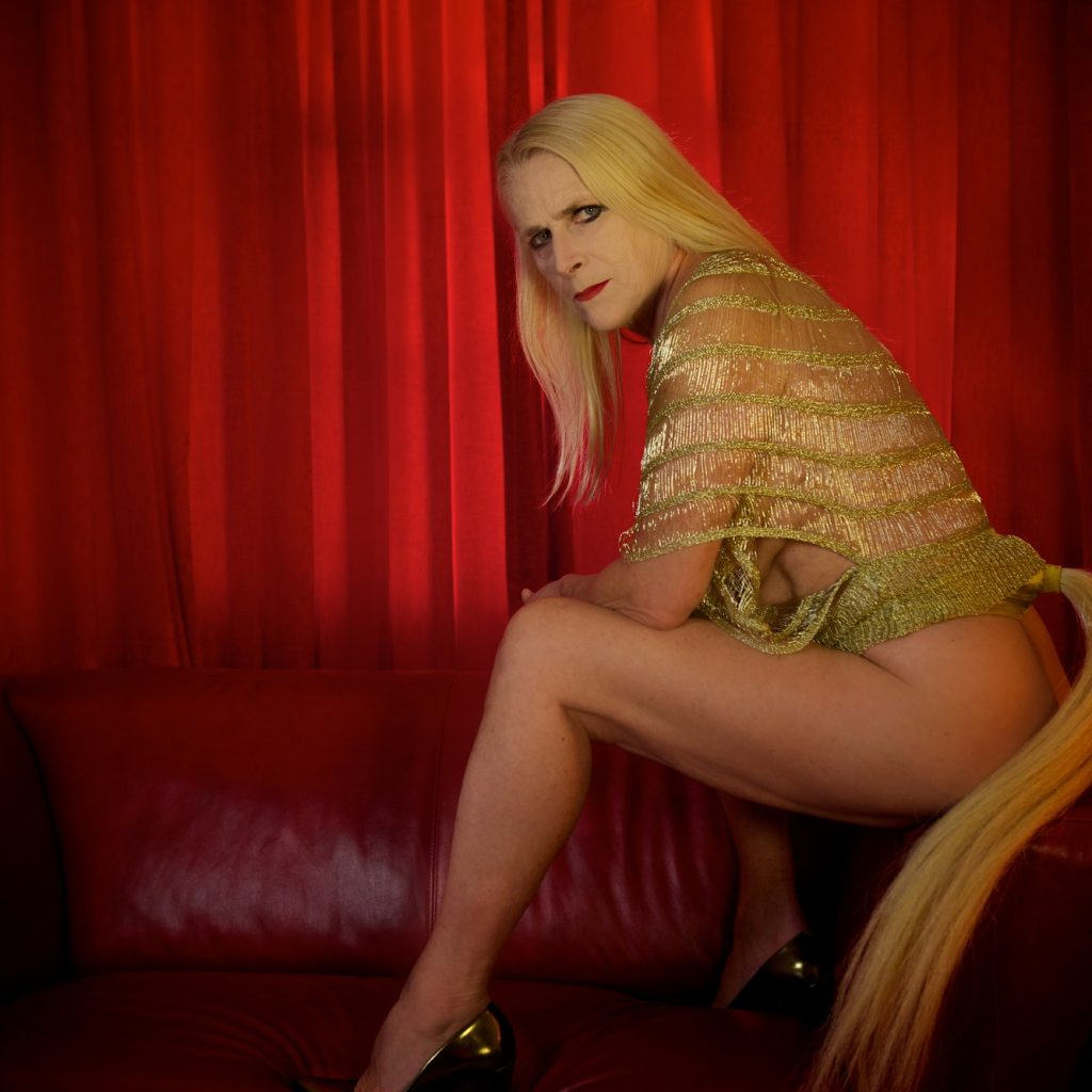 Image of a woman wearing a gold top and gold high heels, naked from the waist down, with long blonde hair, sitting on a red leather sofa.