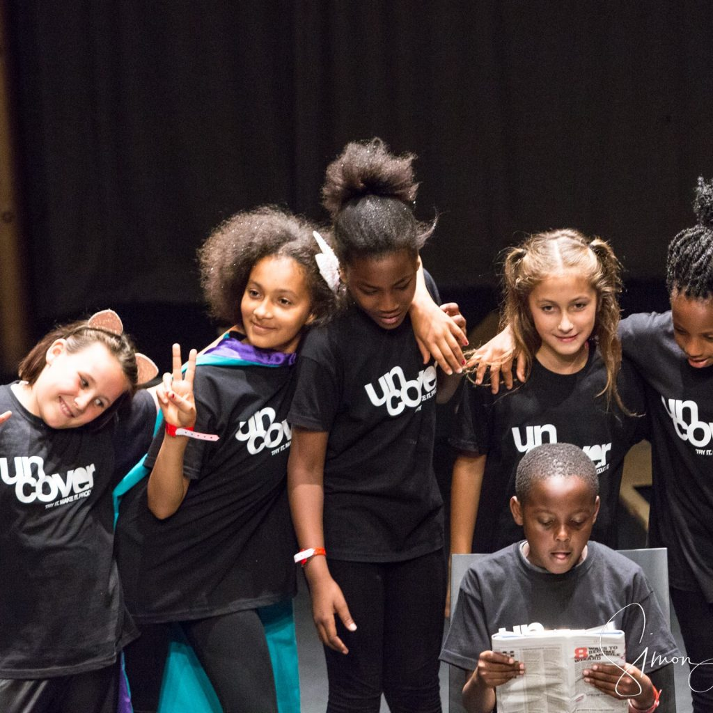 A group of young performers are stood in a line with their arms around each other