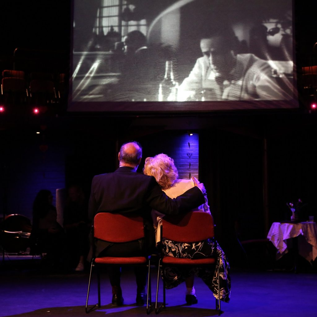 Image of a man and woman, sitting on chairs watching a film, the man has his arm around the woman and her head is on his shoulder.