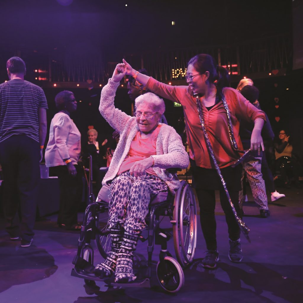 Image of 2 people dancing, one is an older woman in a wheelchair, the other holds her hand and is twirling her.