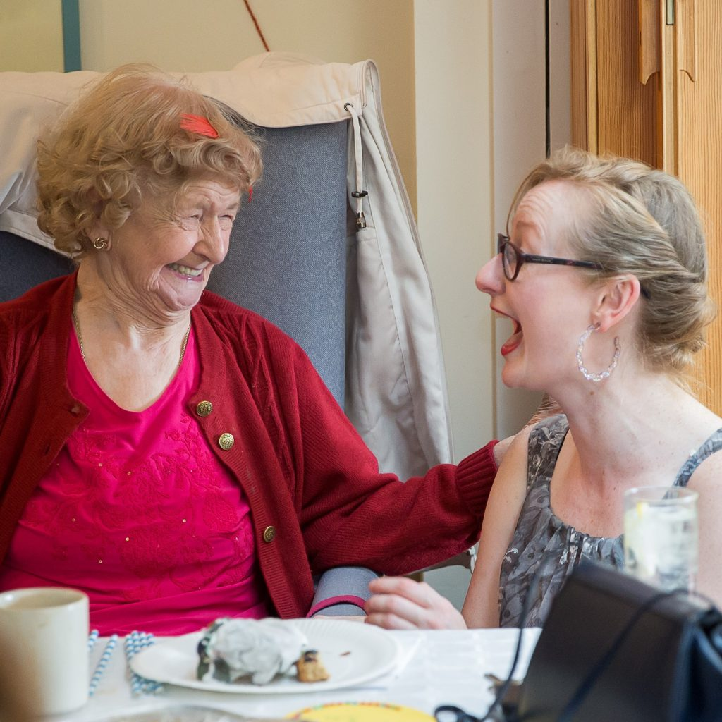 An older and younger woman laugh together.