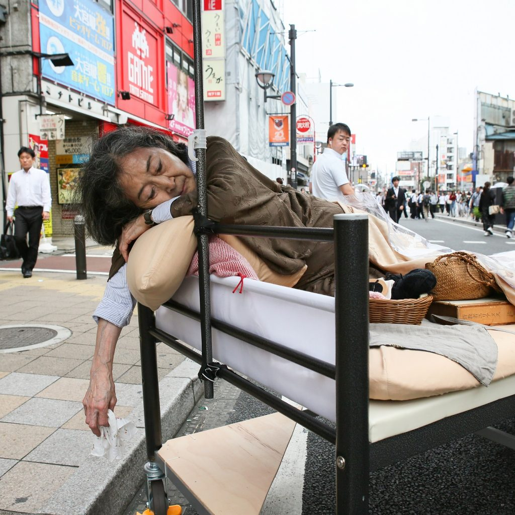Woman lies in a hospital bed in the middle of a busy street.