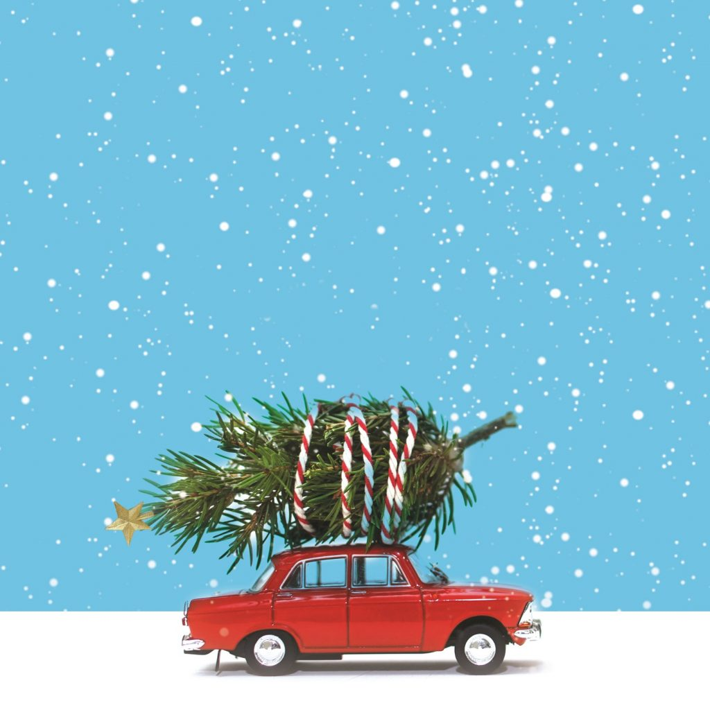 An a image of a red car driving in snow with a Christmas tree wrapped on top of it. s