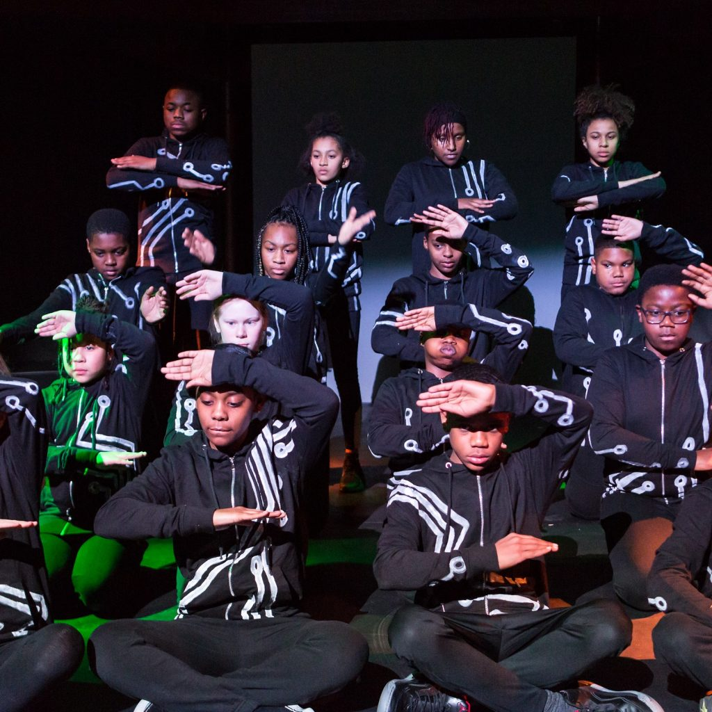 Image of a group of people sitting on stage, doing a dance move with their arms