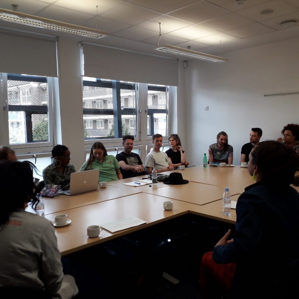 A group of people sitting around a table in a meeting room.